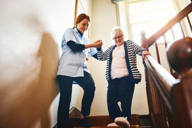 Caregiver helping senior woman walking down stairs stock photo