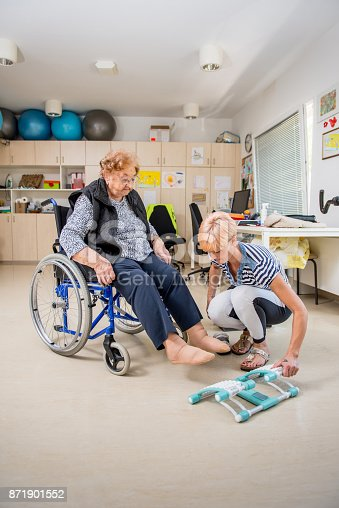 912333752 istock photo Caregiver Helping Senior Woman With Phisyotherapy Exercise 871901552
