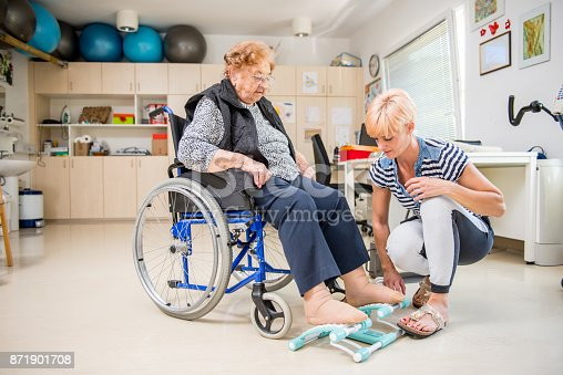 912333752 istock photo Caregiver Helping Senior Woman With Phisyotherapy Exercise 871901708