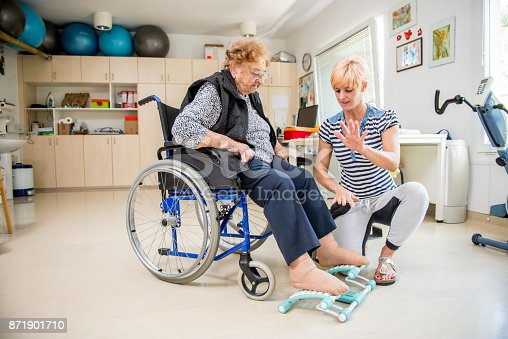 912333752 istock photo Caregiver Helping Senior Woman With Phisyotherapy Exercise 871901710