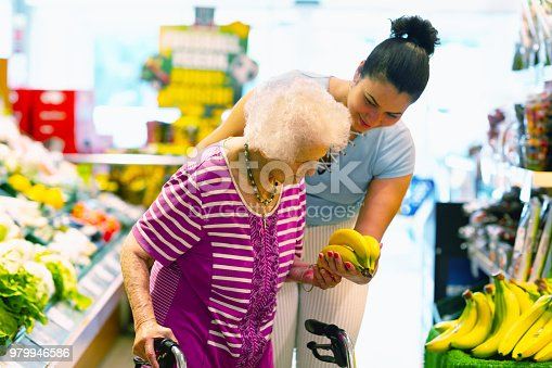 Young hispanic caregiver supporting senior woman, 93 years, with buying banans in a shop