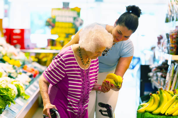 caregiver helping senior woman with shopping stock photo