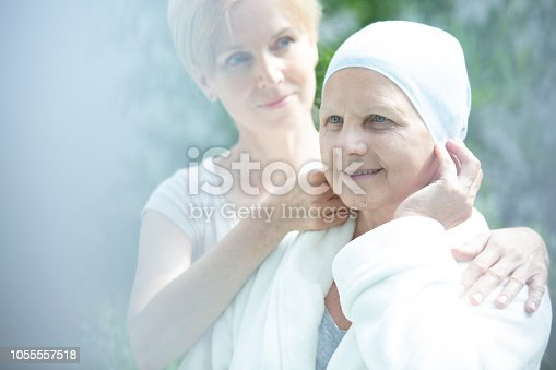 928968772 istock photo Caregiver helping sick elder woman with lung cancer 1055557518