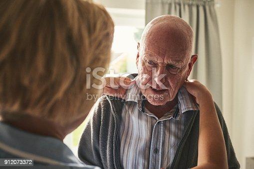 Senior man at care home being dressed by female caregiver. Caregiver helps dressing elderly patient.