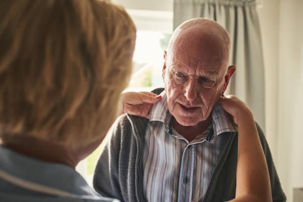Soignant aide patiente âgée de pansement à domicile - Photo