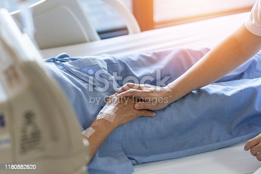 958891774istockphoto Caregiver holding elderly senior patient (ageing old adult person) hand in hospital bed or nursing hospice, geriatrician palliative home, while caretaker having  medical health care service 1180882620