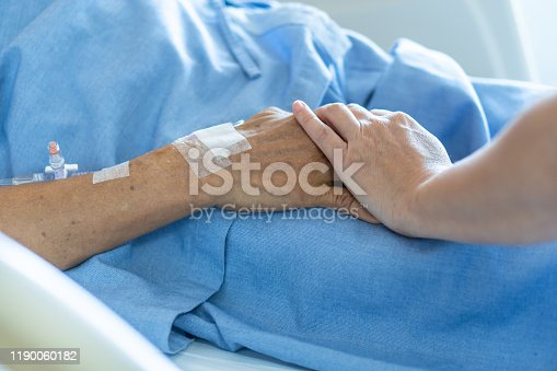 958891774istockphoto Caregiver holding elderly senior patient (ageing old adult person) hand in hospital bed or nursing hospice, geriatrician palliative home, while caretaker having  medical health care service 1190060182