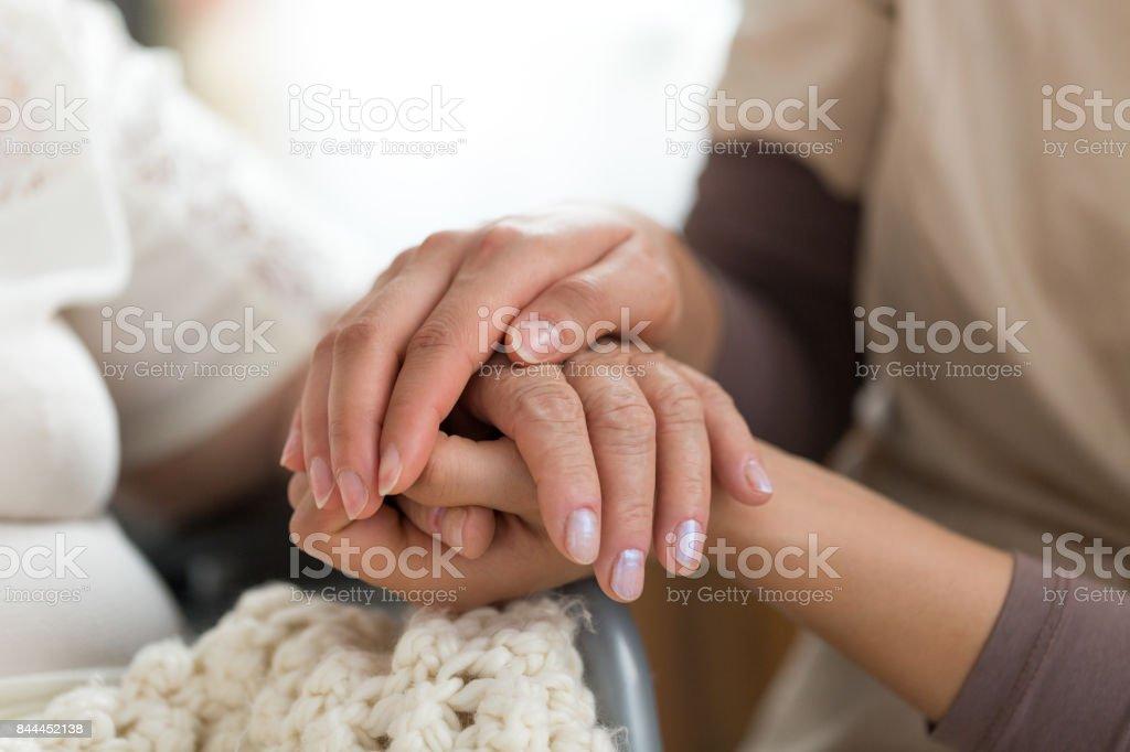 Caregiver holding senior woman's hands stock photo