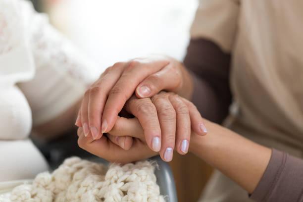 pflegeperson senior frau händchenhalten - hospiz stock-fotos und bilder