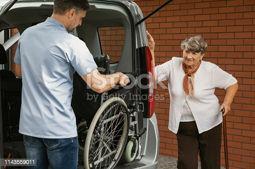 istock Caregiver holding wheelchair in the car for disabled elderly woman with walking stick 1143559011