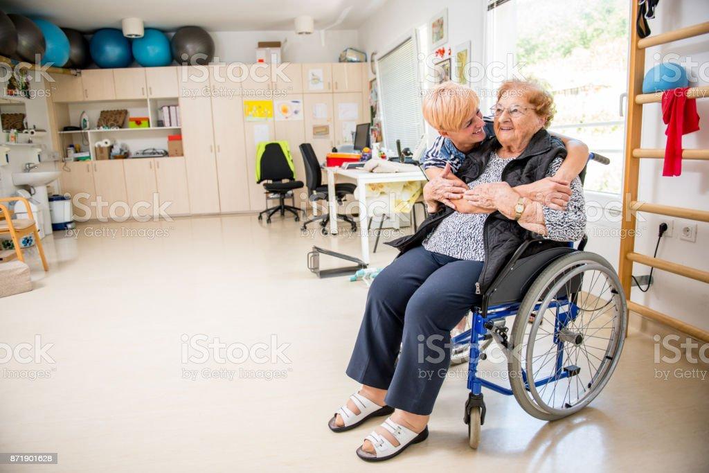 Caregiver Hugging a Senior Woman at Retirement Home.