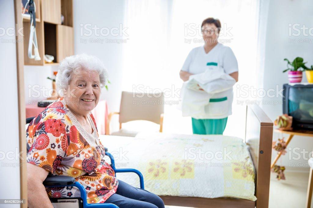 Caregiver In The Nurse Home Preparing Bed For A Senior Women