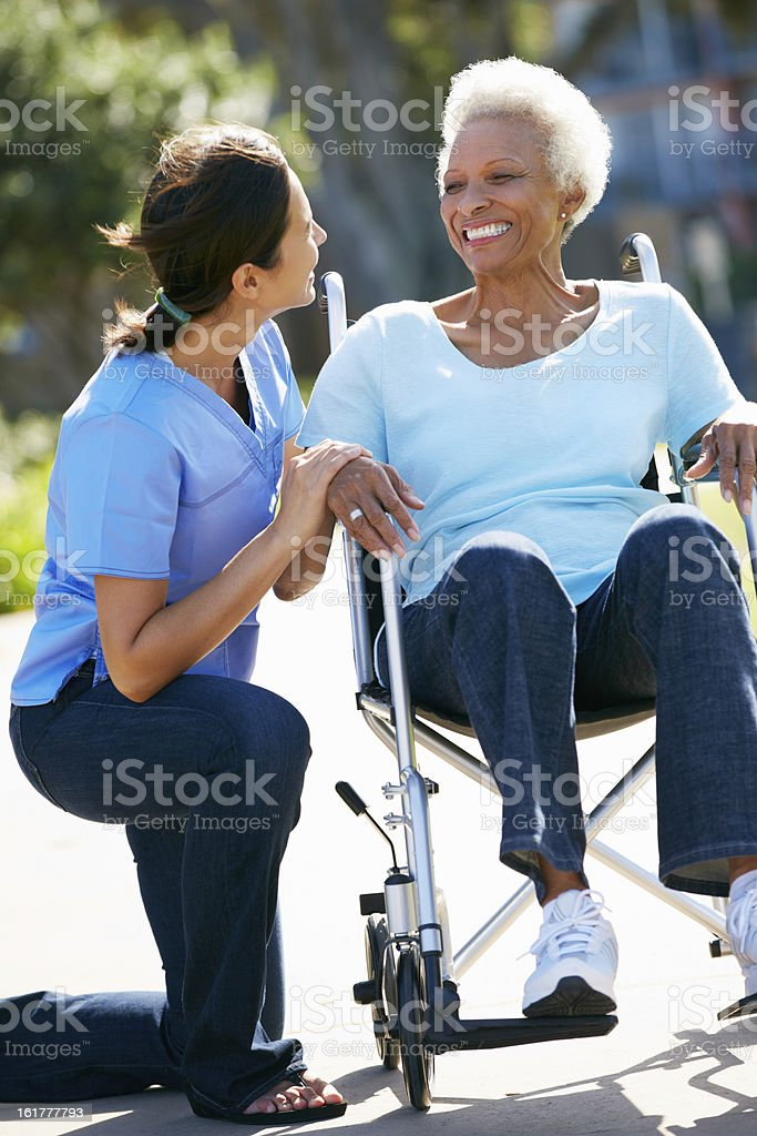 Caregiver kneeling and talking to senior woman in wheelchair stock photo