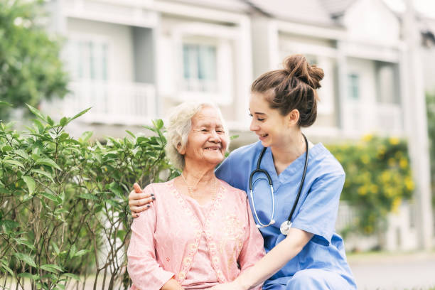 Caregiver laughing with Asian elderly woman stock photo