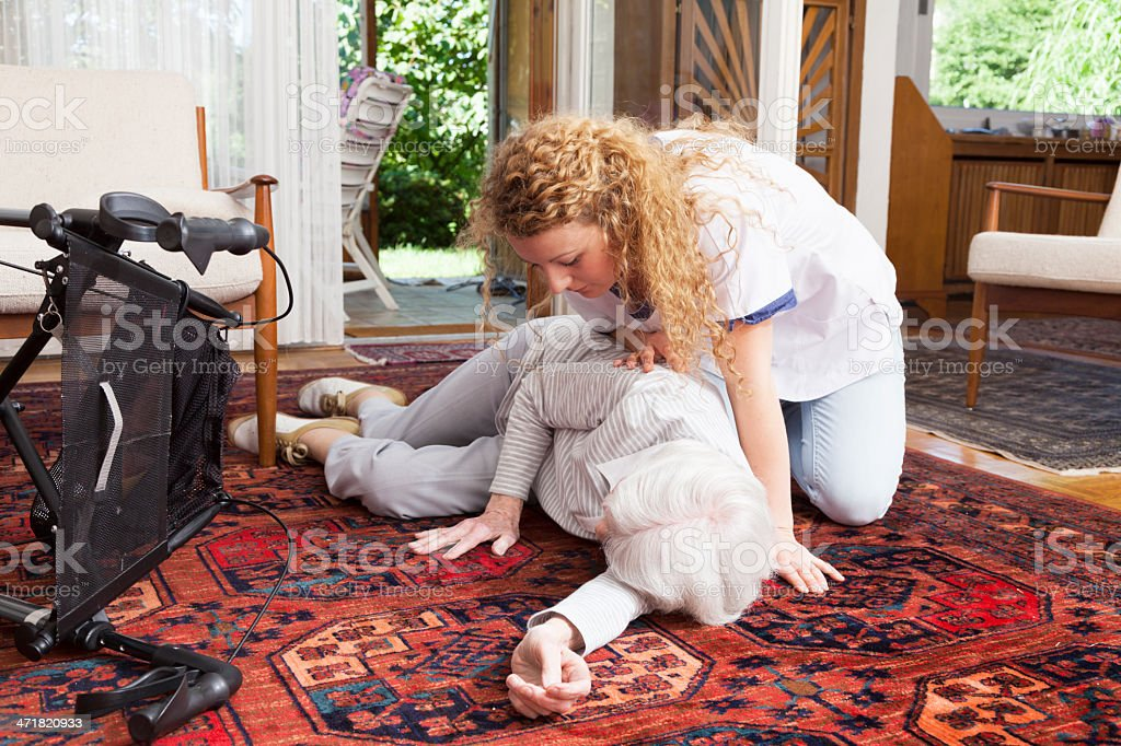 caregiver looking at senior woman after accident stock photo