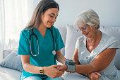 介護者は、年配の女性は家庭での血圧測定します。