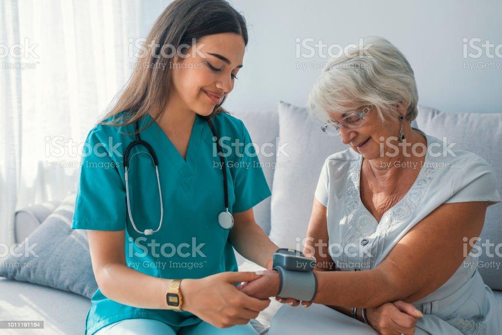 Medición de la presión arterial de la mujer mayor en casa de cuidador. - foto de stock