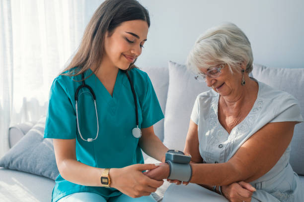 caregiver measuring blood pressure of senior woman at home. - female nurse stock photos and pictures