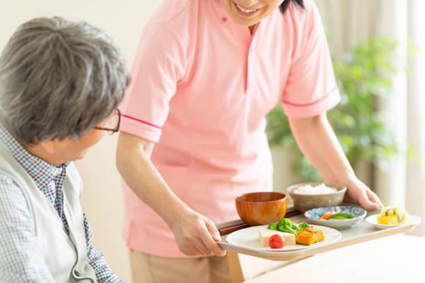 食事の準備をする介護者 - 介護士 ストックフォトと画像
