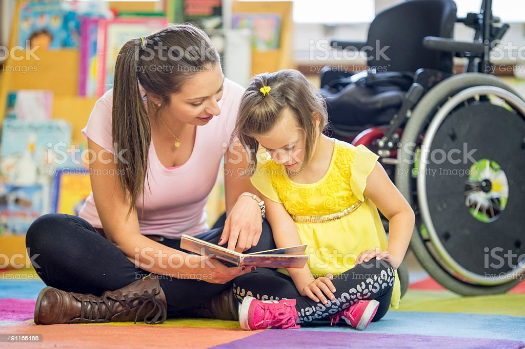 A caregiver and a little girl with cerebral palsy are sitting on the...