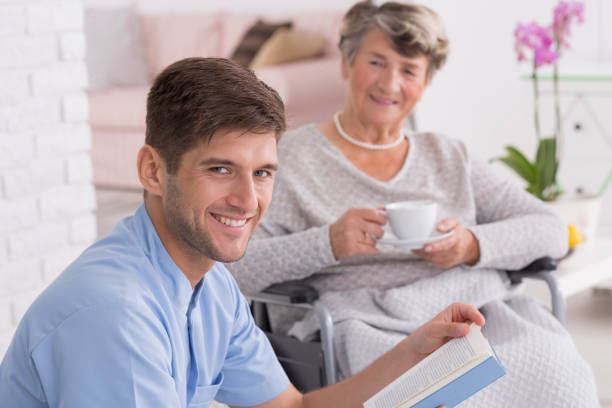 caregiver reading to senior lady with tea - psychiatric ward stock photos and pictures