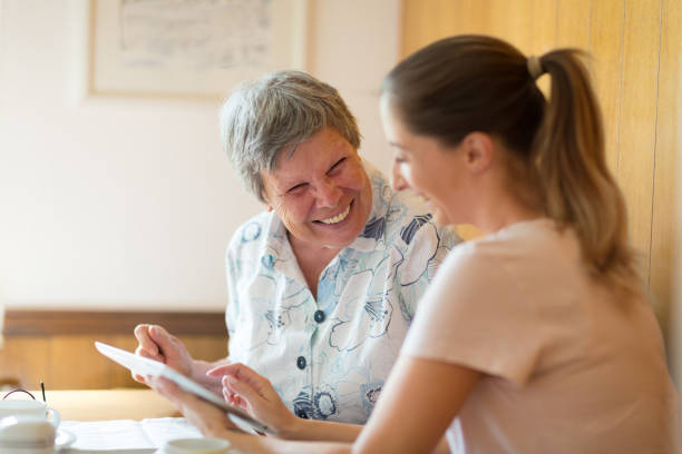 caregiver showing digital tablet to senior woman stock photo