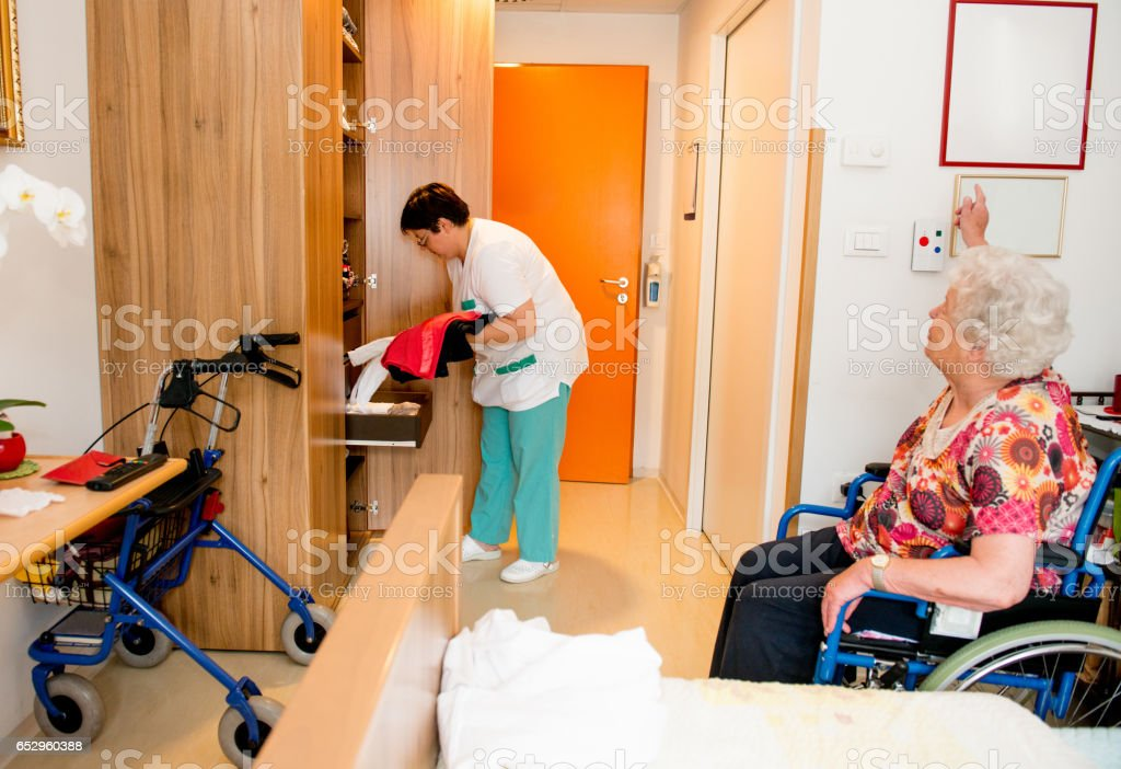 Caregiver Socializing With Senior Woman While Cleaning Her Room stock photo