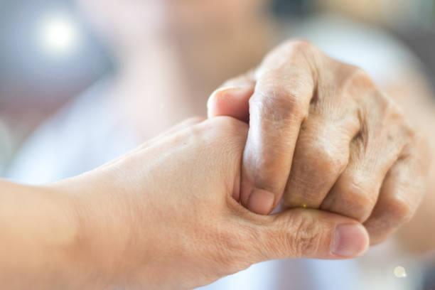 cuidador, asistencia especializada, cuidadora de manos de la mano del anciano en el cuidado de hospicios. bondad filantrópicas al concepto de discapacitados. semana de reconocimiento de servicio público - memorial day fotografías e imágenes de stock