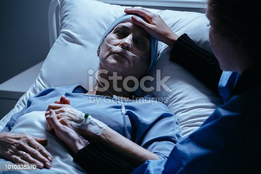 928968772 istock photo Caregiver supporting sick woman with cancer dying in the hospital 1010338970