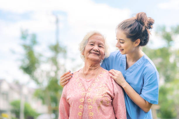 caregiver take care of Asian elderly woman outdoor stock photo