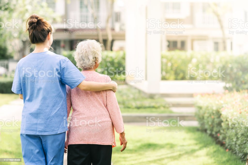 caregiver walking with elderly woman outdoor - Royalty-free Adulto Foto de stock