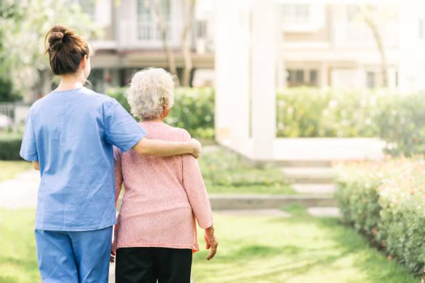 vårdgivare gå med äldre kvinna utomhus - omsorg bildbanksfoton och bilder