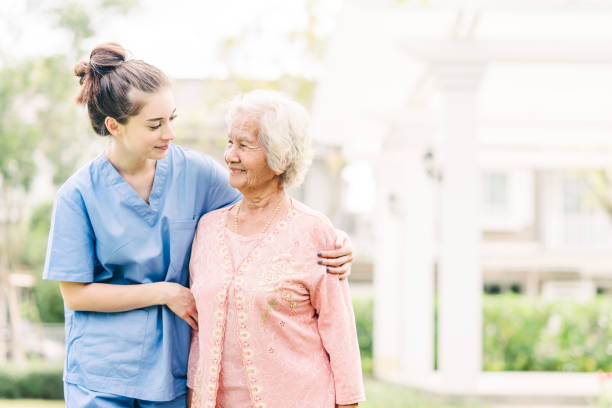 caregiver with Asian elderly woman outdoor stock photo