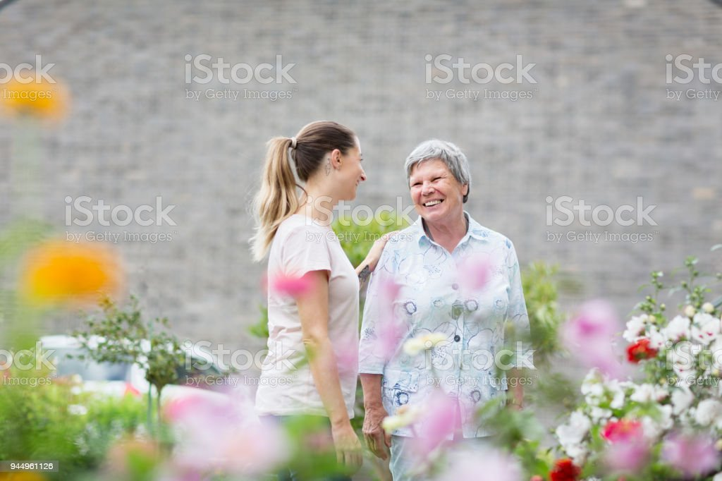 caregiver with senior adult outdoors in garden stock photo