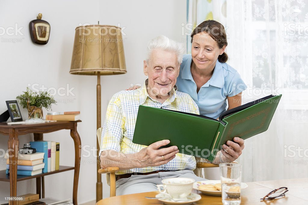 Caregiver with senior man and old photo album royalty-free stock photo