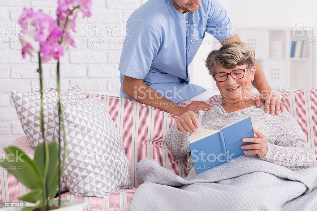 Caregiver with senior reading a book photo libre de droits