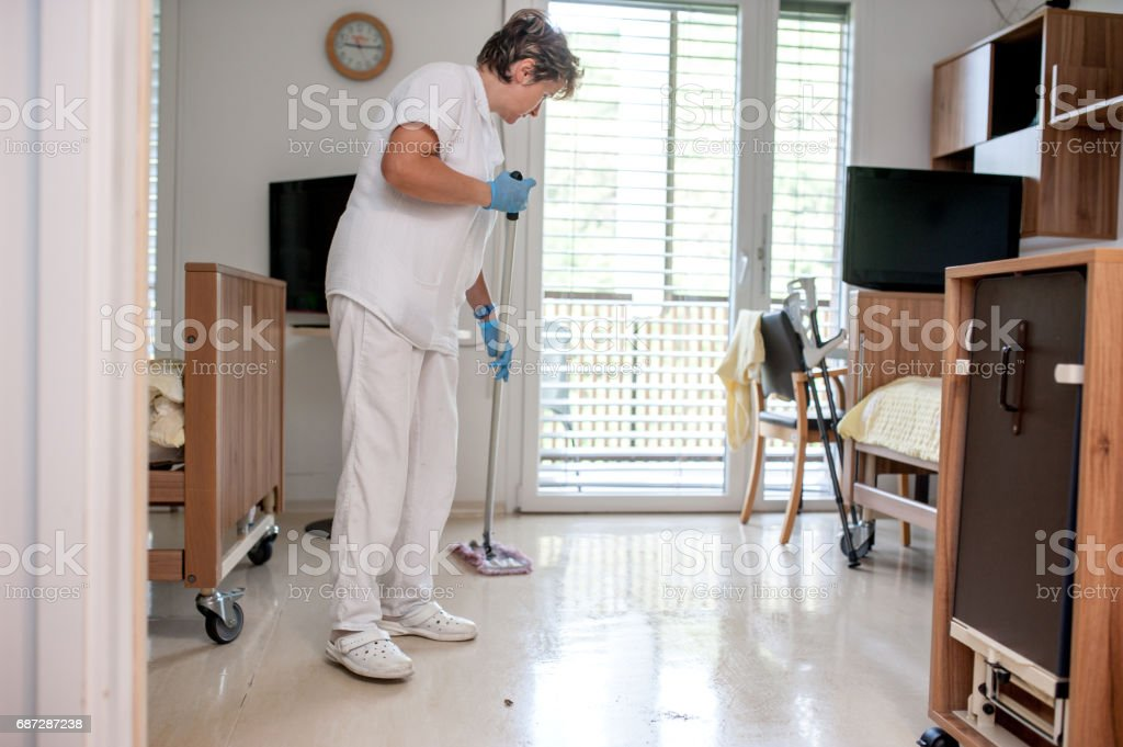 Caregiver Woman Cleaning Bedroom In The Retirement Community stock photo