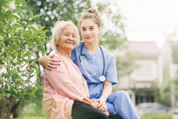 Caregiver woman happy to take care elderly  patient stock photo