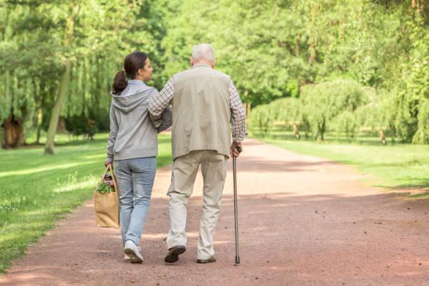 Betreuer – Frau hilft älteren Mann beim Einkaufen – Foto