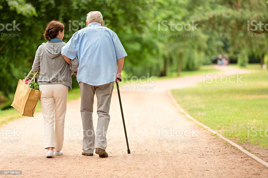 Caregiver – woman helping senior man with shopping stock photo