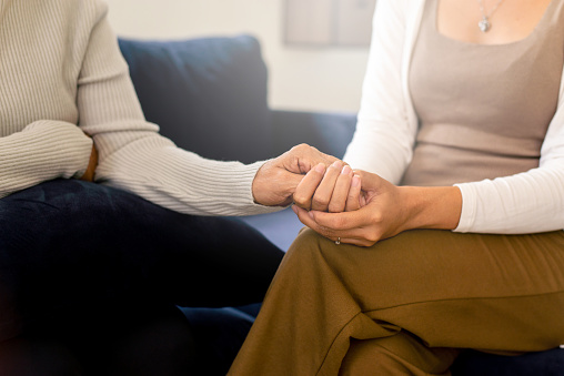 Caregiver women holding hands to elderly with alzheimer disease at home,Adult social care concept