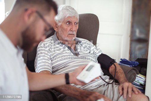 a Senior man receiving physical therapy at home.