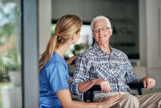 Caregivers make a difference everyday Shot of a senior man in wheelchair being assisted by his female nurse neurodegenerative disease stock pictures, royalty-free photos & images