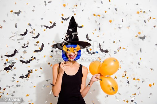 1016084100istockphoto Careless, carefree, concept. Portrait of magnificent lady with red lipstick hold orange helium blow ballons in hands, hide face on mask with wooden stick isolated on white background 1048226462