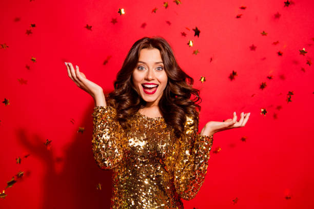 careless, carefree, dream, dreamy concept. beautiful, attractive, pretty, charming, modern wave hairstyle lady look at camera with raised hands up and open mouth isolated on shine red background - smile woman open mouth foto e immagini stock