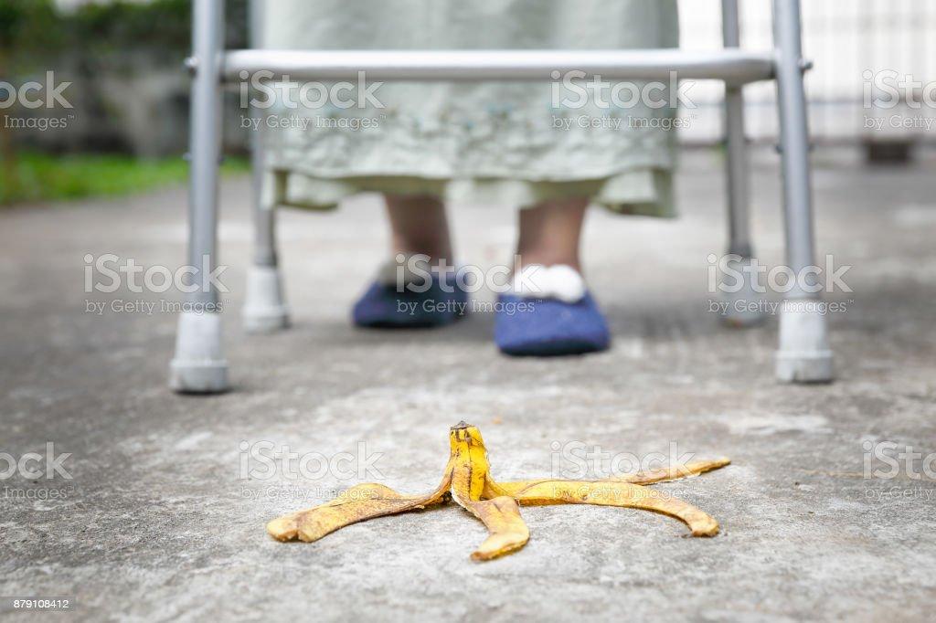 Unvorsichtige Seniorin Schritt über eine Bananenschale auf Gehweg – Foto