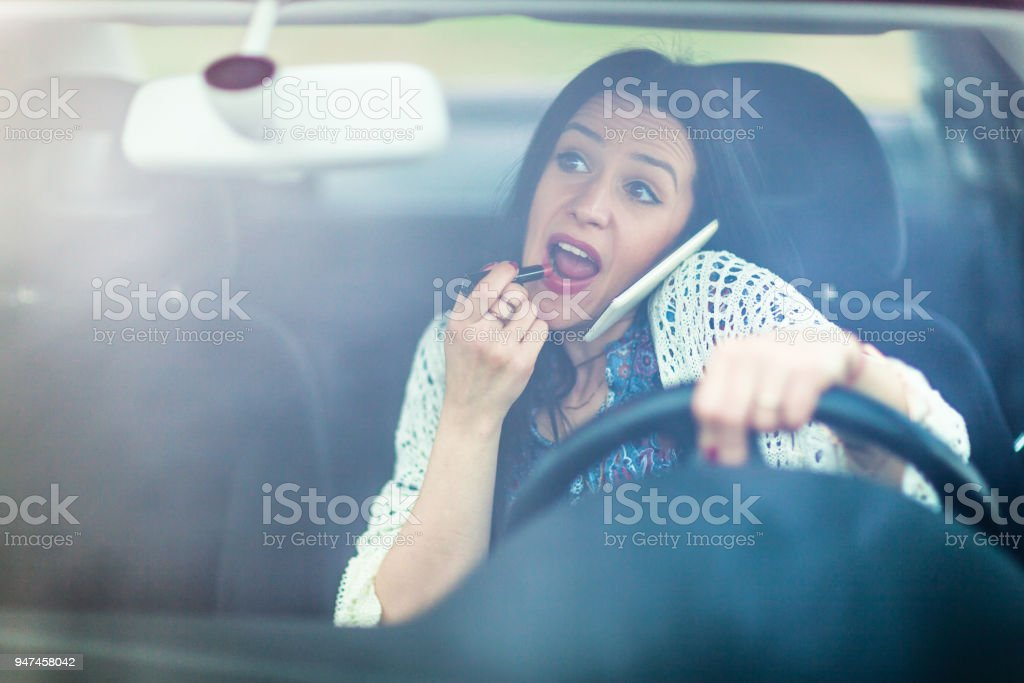Mulher jovem descuidada aplicando fazer acima e falar ao telefone enquanto dirige - foto de acervo