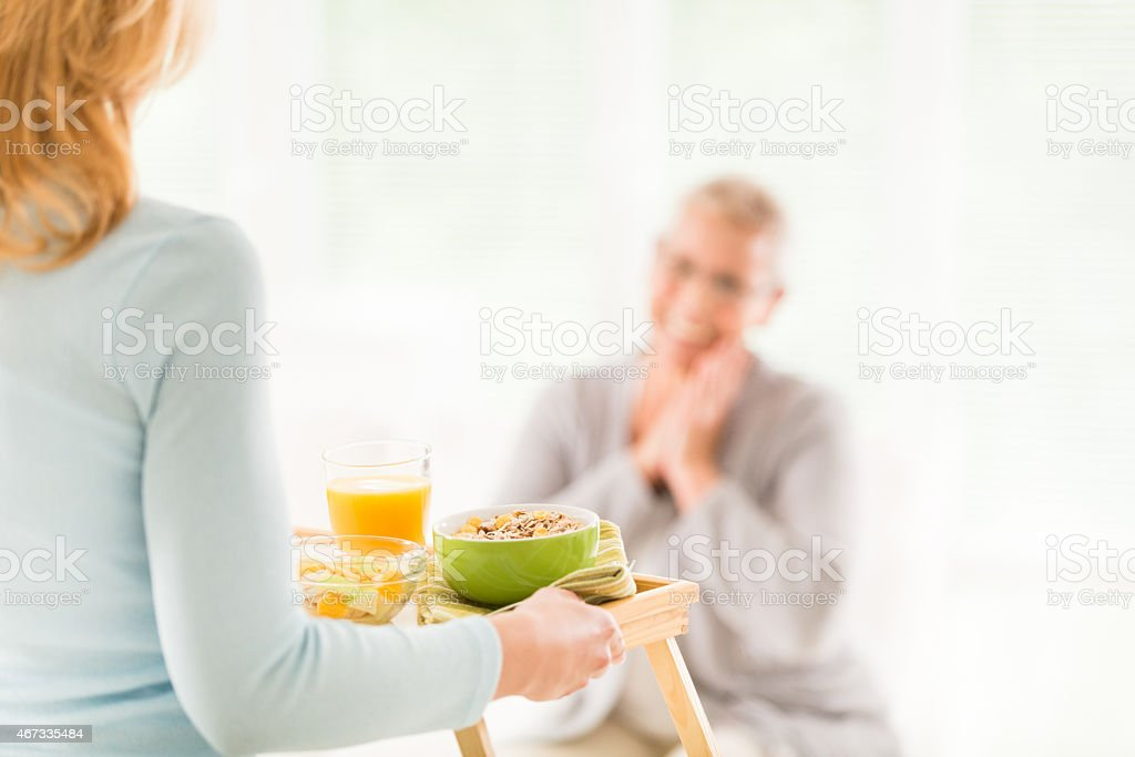 Carer bringing breakfast to a senior woman stock photo