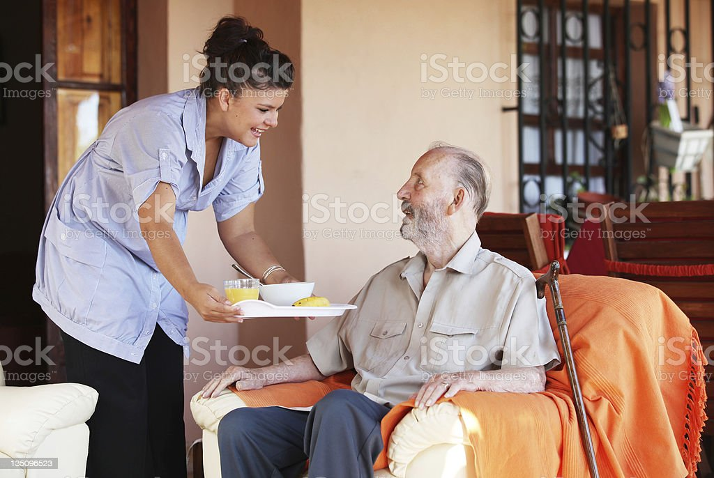carer bringing meal to senior stock photo