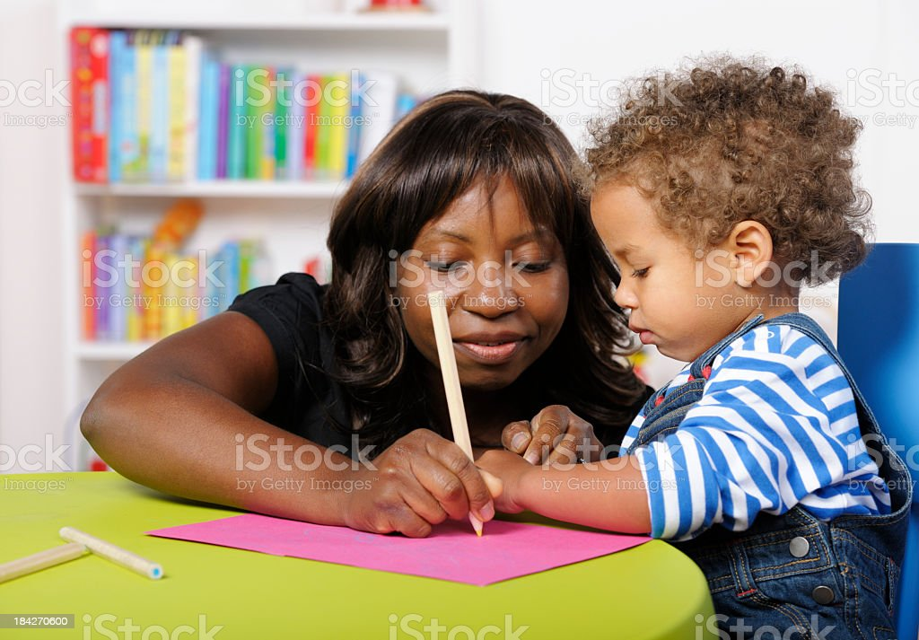 Carer/ Childminder/ Teacher Showing Toddler How To Draw royalty-free stock photo